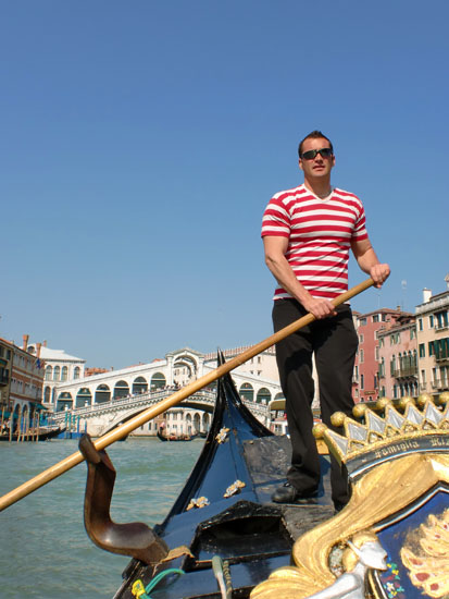 Gondolier in red and white stripy top in Venice, Italy