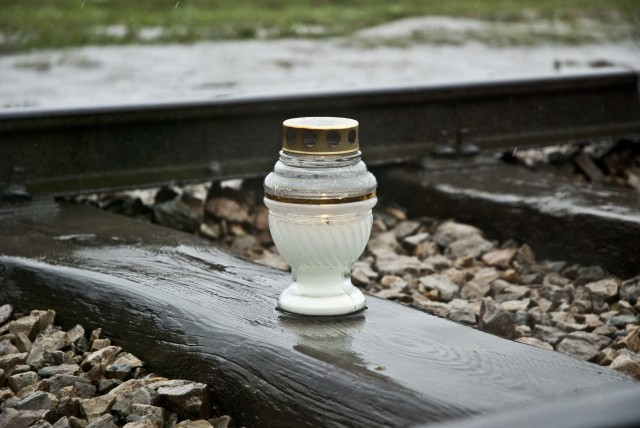 Candle on train track at Birkenau, Auschwitz II