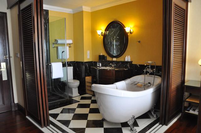黑白方格的地板,卧床是四根柱子的老式设计,开放式浴室可选择把百叶